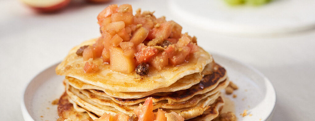 A stack of Apple Pie Protein Pancakes topped with an apple compote on a white plate
