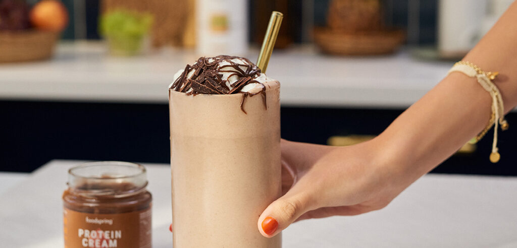 A white hand reaches for a banoffee shake in a glass.