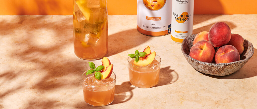 peach kombucha basil lemonade in a pitcher and two glasses garnished with peach slices and basil leaves