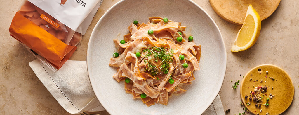 cauliflower pasta alfredo studded with bright green peas and green herbs