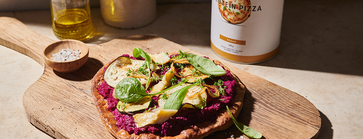 vegetable pizza topped with purple pesto