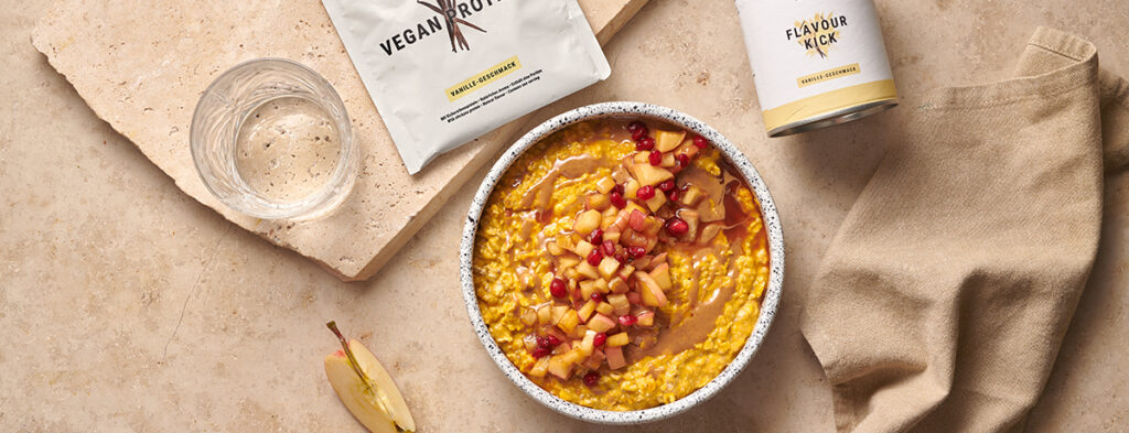 a hearty orange tinted bowl of Pumpkin Spice Overnight Oats seen from above.