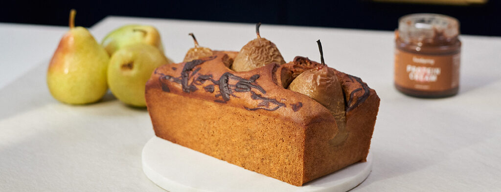 A loaf-shaped nut cake with poached, sunken pears peeking out of the top. Two pears sit behind it on the left side, and a jar of Protein Cream on the right.