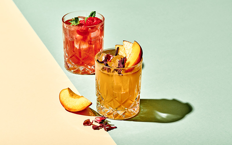 Two clear glasses of Clear Whey in iced-tea brown and raspberry-red, garnished with fresh peaches and mint