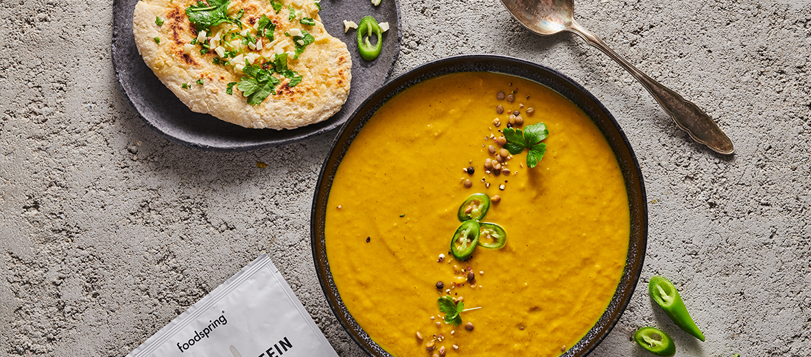 A rich orange bowl of mulligatawny soup with the corner of a protein naan visible in the corner of the frame