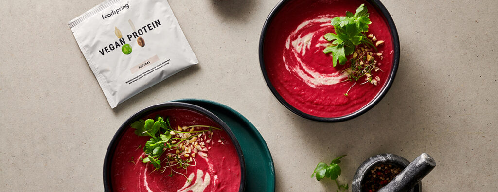 A bowl of vibrant red beet soup with a subtle white cashew swirl, topped with fresh herbs.