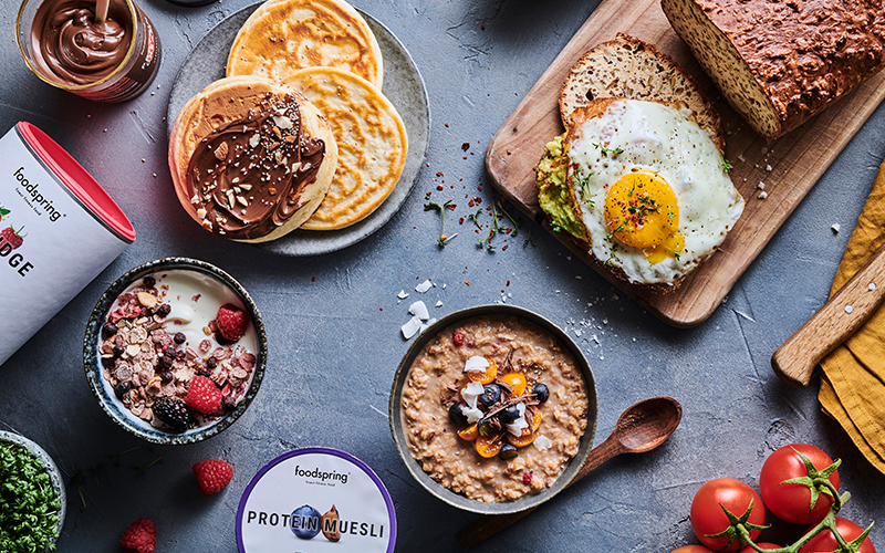 A table loaded with delicious breakfast items: a fried egg, protein bread, protein porridge, protein muesli, protein pancakes