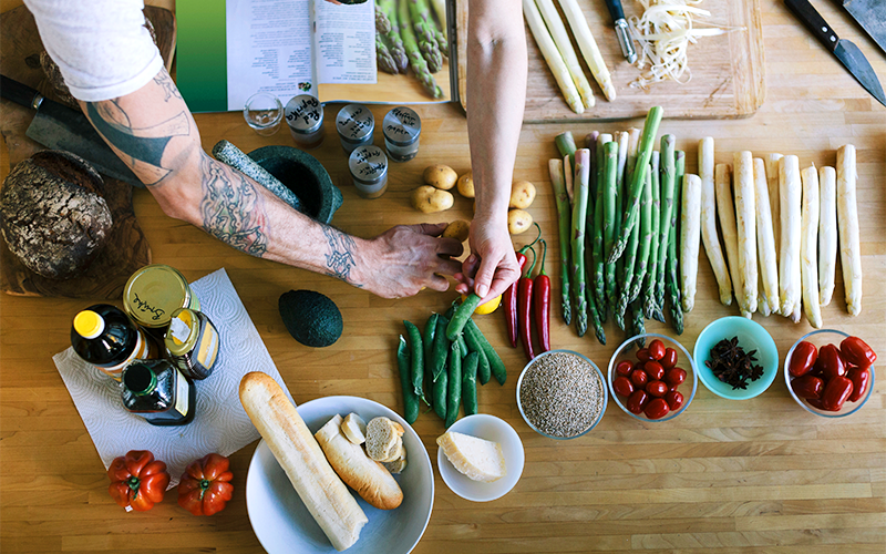 A pair of white-skinned arms, one with tattoos, reaches over a wooden countertop laid with foods for a weight loss meal plan