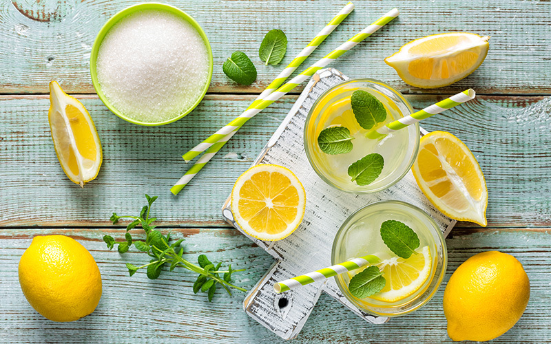 A setup of lemonade: lemon halves and quarters, sprinkled with paper straws and mint leaves, and a bowl with powdered sweeteners