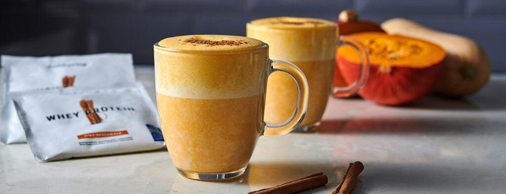 Two glass mugs full of an orange-tinted Pumpkin Spice Latte