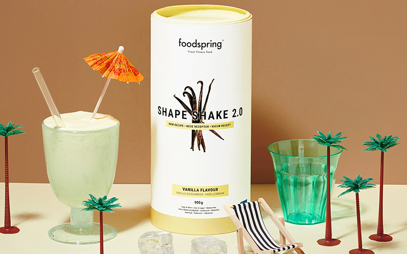 A canister of shape shake 2.0, a source of inulin. There are toy palm trees to the side, and a glass of prepared Shape Shake 2.0 with a cocktail umbrella sticking out.