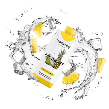 CocoWhey packaging in the midst of flowing water and pineapple chunks